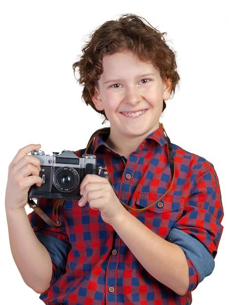 Freundliches lächelndes kind (junge) eine sofortige kamera anhalten Premium Fotos