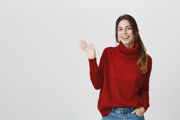 Freundliches mädchen im pullover winkt hand, sag hallo Kostenlose Fotos