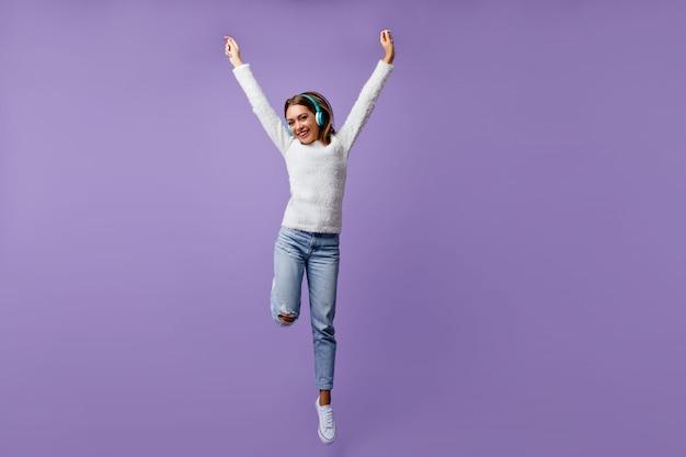 Freundliches mädchen in fröhlicher stimmung springt mit erhobenen armen. porträt des studenten in voller länge im weißen gespräch, das musik hört Kostenlose Fotos