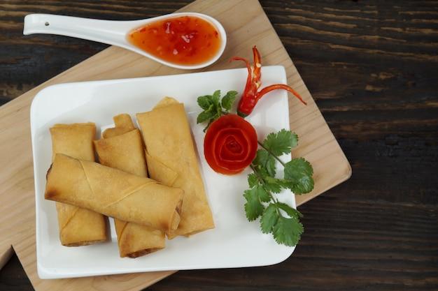 Fried chinese-frühlingsrollen dienten mit chili-sauce auf hölzernem brett auf dunklem holztisch Premium Fotos