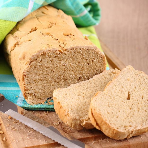 Frisch aus dem ofen glutenfreies brot auf einem schneidebrett Premium Fotos