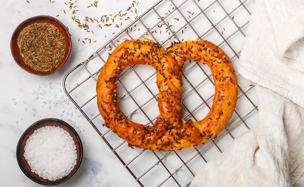 Frisch gebackene brezel mit grobem salz und kreuzkümmel, gourmet-snacks und zutaten am tisch Premium Fotos