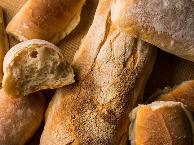 Frisch gebackene brotlaibe auf dunklem hölzernem der leinwand. italienische bäckereiprodukte der beschaffenheitsnahaufnahme Premium Fotos