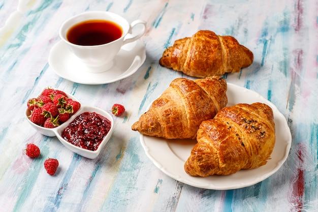 Frisch gebackene croissants mit himbeermarmelade und himbeerfrüchten. Kostenlose Fotos