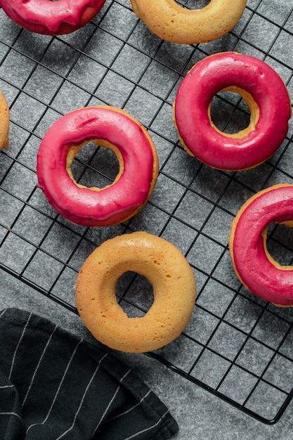 Frisch gebackene donuts mit leuchtend rosa zuckerguss auf kühlregal Premium Fotos