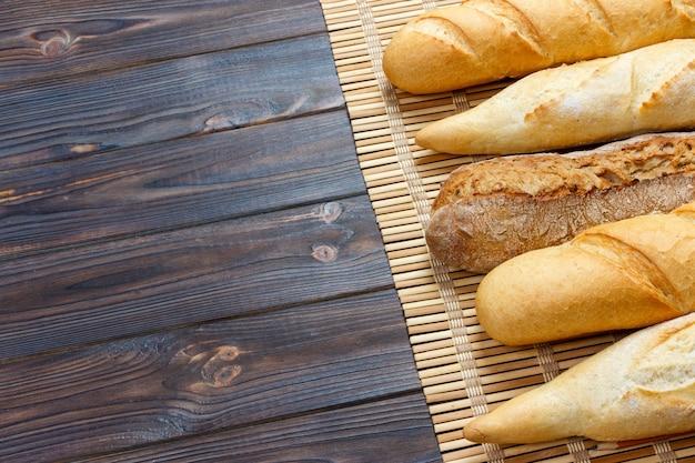 Frisch gebackene französische stangenbrote auf weißem holztisch. ansicht von oben Premium Fotos