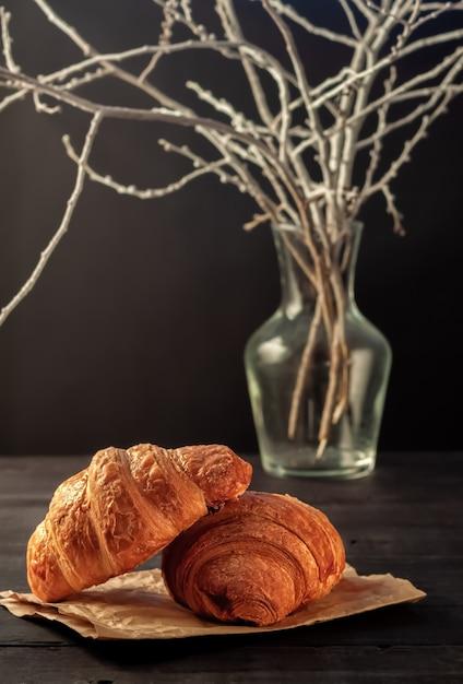 Frisch gebackene hausgemachte knusprige croissants auf einem schwarzen tisch Premium Fotos