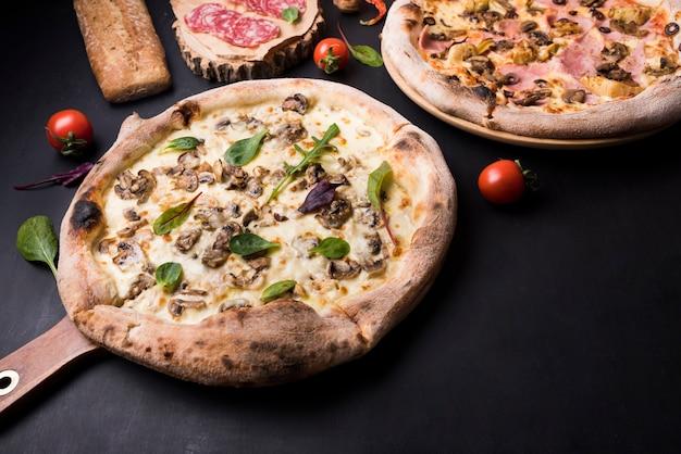 Frisch gebackene italienische pizza; pepperoni- und kirschtomate über schwarzer oberfläche Kostenlose Fotos