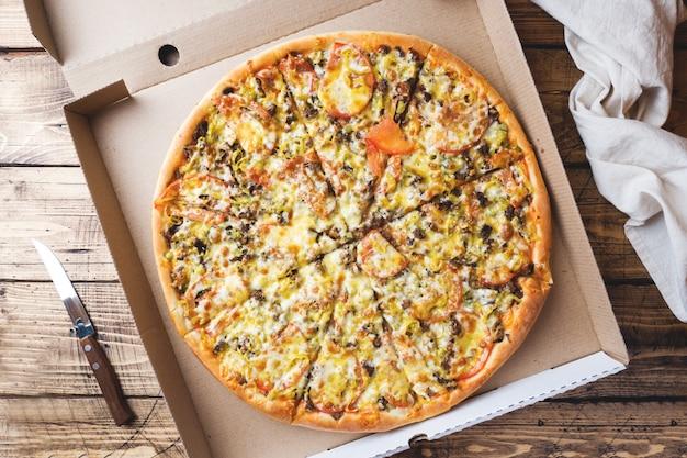 Frisch gebackene pizza in einer pappschachtel auf einem holztisch. Premium Fotos