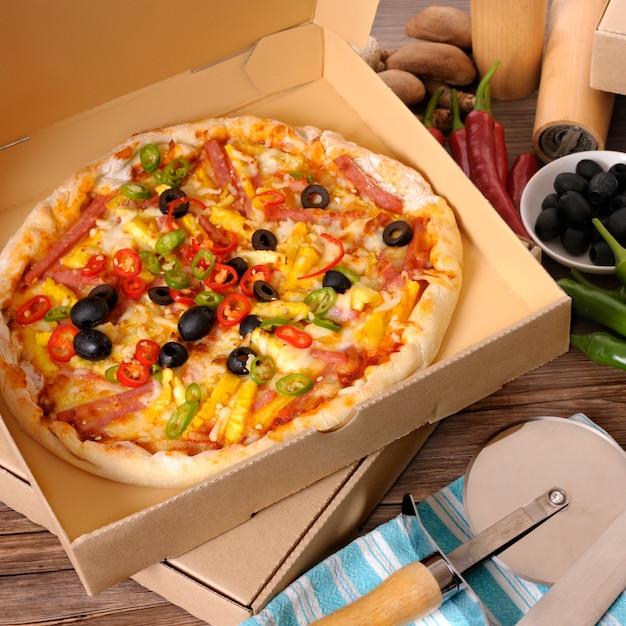 Frisch gebackene pizza in lieferbox mit zutaten. Kostenlose Fotos