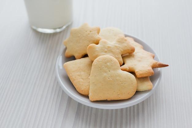 Frisch gebackene selbst gemachte plätzchen und ein glas milch auf weißem holz Premium Fotos