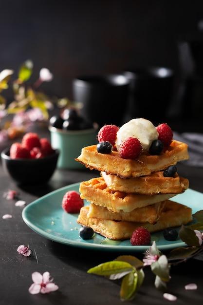 Frisch gebackene waffeln mit himbeeren, beeren, honig und kaffee zum frühstück oder brunch Premium Fotos