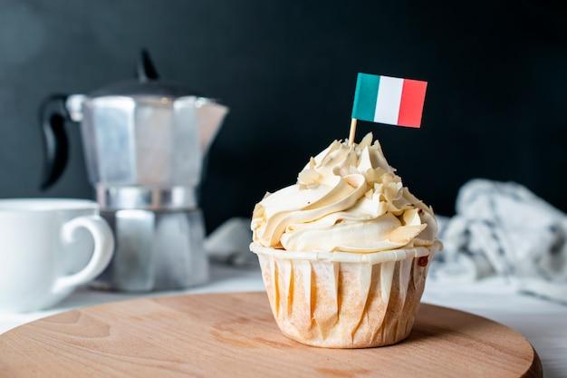 Frisch gebackener mandelcreme-kleiner kuchen und mandelkrume mit italienischer flagge für morgen-teeparty Premium Fotos
