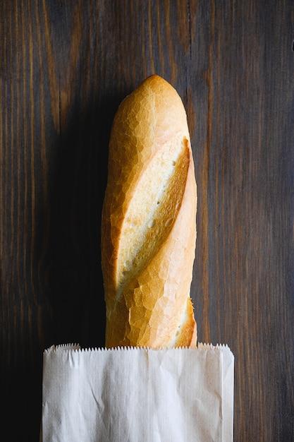Frisch gebackenes brot in einer papiertüte auf einem holztisch Premium Fotos