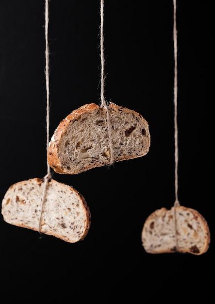 Frisch gebackenes brot mit dem hafer, der am seil auf schwarzem hintergrund hängt Premium Fotos