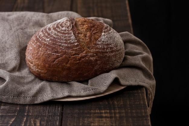 Frisch gebackenes brot mit geschirrtuch auf dunklem hölzernem brett Premium Fotos