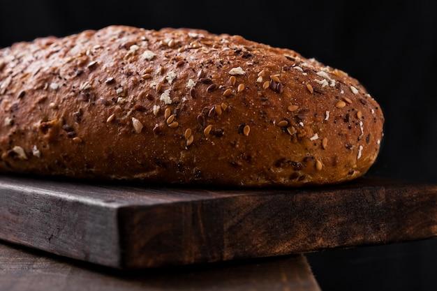 Frisch gebackenes brot mit hafer auf hintergrund des hölzernen brettes Premium Fotos