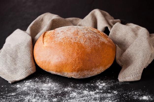 Frisch gebackenes brot mit mehl und geschirrtuch auf schwarzem hintergrund Premium Fotos