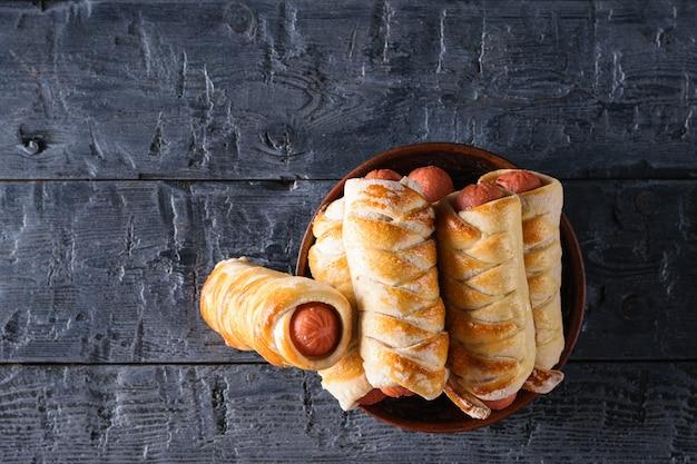 Frisch gekochte selbst gemachte wurstrollen in einer lehmschüssel auf einem dunklen holztisch. Premium Fotos