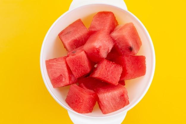 Frisch geschnittene wassermelone der draufsicht innerhalb der weißen plastikplatte auf gelbem, fruchtfarbenem sommer Kostenlose Fotos