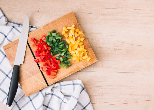 Frisch geschnittenes bio-rot; gelbe und grüne paprikaschoten auf schneidebrett mit messer über dem holzschreibtisch Kostenlose Fotos
