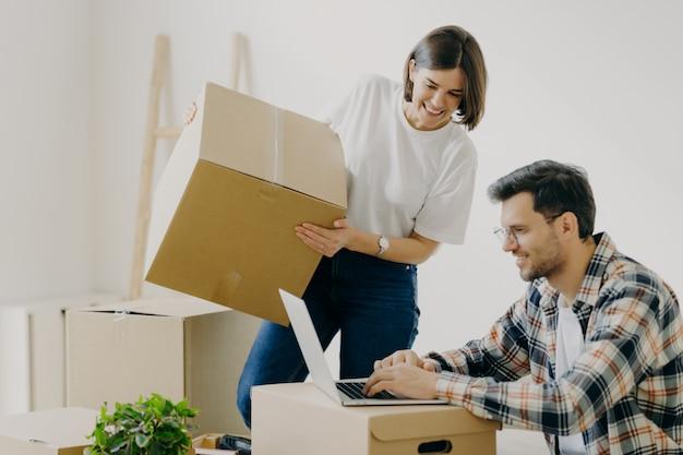 Frisch verheiratete familienpaare posieren in ihrer neuen wohnung, packen kartons mit habseligkeiten aus Premium Fotos