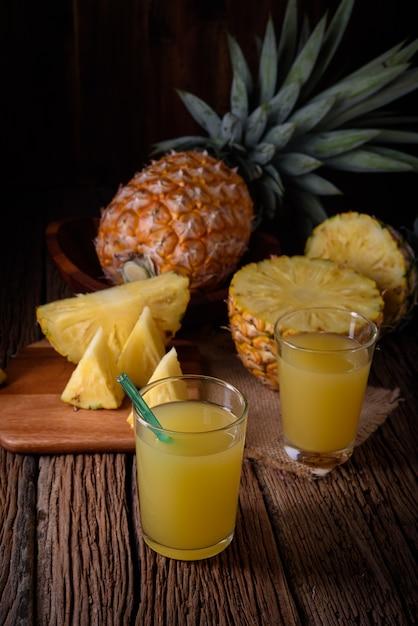 Frische ananas und saft auf holztisch. Premium Fotos