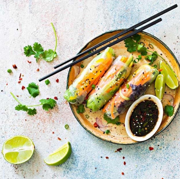 Frische asiatische vorspeise frühlingsrollen (nem) aus reispapier und rohem gemüse und kräutern mit scharfer soße auf hellblauem hintergrund. Premium Fotos