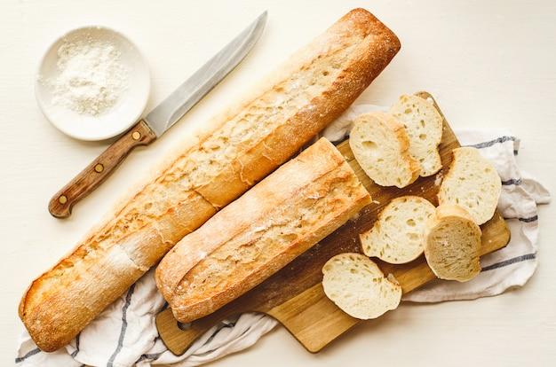Frische baguettes mit einer knusprigen kruste, gehackt auf einem schneidebrett Premium Fotos