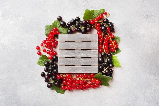 Frische beeren von schwarzen und roten johannisbeeren auf grauer tabelle mit kopienraum. Premium Fotos