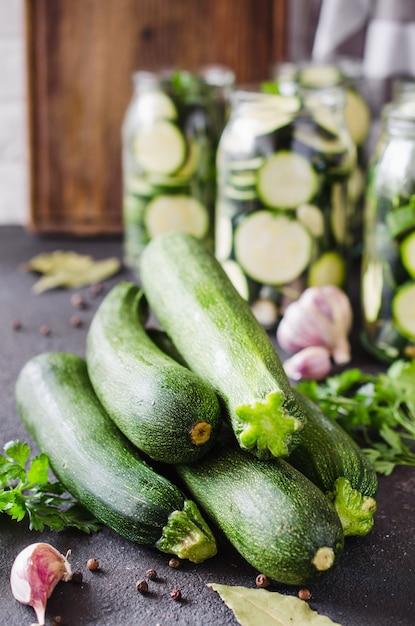 Frische bio-zucchini, knoblauch und petersilie, kräuter und gewürze. Premium Fotos