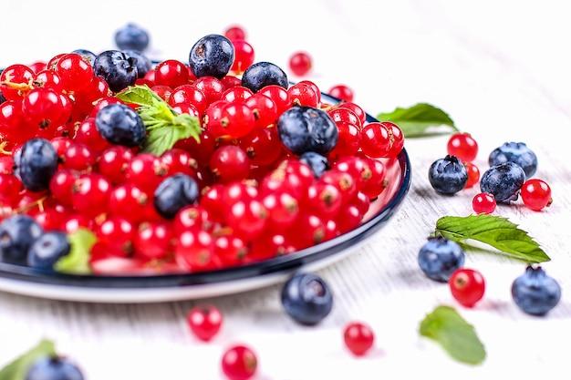Frische blaubeeren und rote johannisbeeren mit tadellosen blättern in einer hölzernen schüssel auf leinwand. diätfutter, vegane beeren Premium Fotos