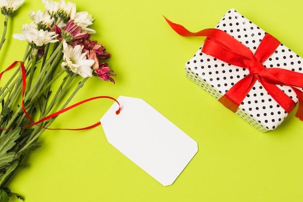 Frische blumen mit weißem tag und dekorativer geschenkbox auf grüner oberfläche Kostenlose Fotos