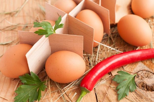 Frische braune eier, petersilie und chili Premium Fotos