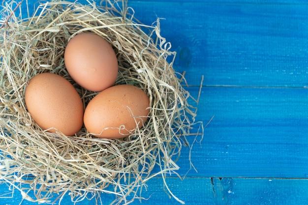 Frische braune hühnereien im heu nisten auf blauem hölzernem hintergrund. Premium Fotos