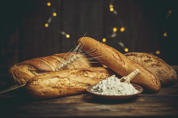 Frische brote mit weizen und gluten auf einem holztisch Premium Fotos
