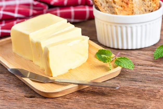 Frische butter schnitt mit messer auf hölzerner platte und brot. Premium Fotos