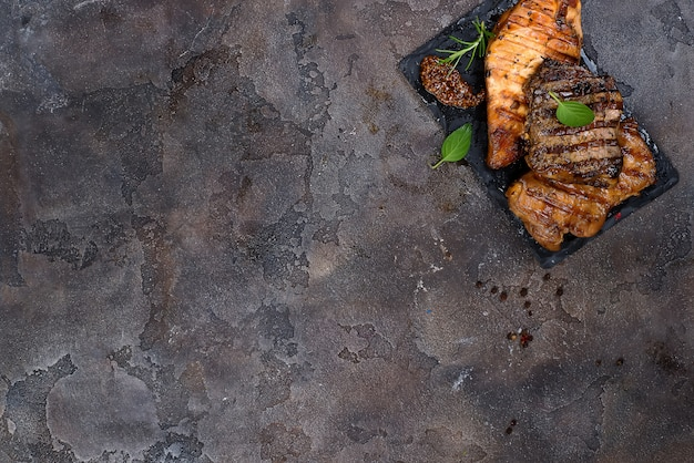 Frische drei arten gegrilltes steak (huhn, schweinefleisch, rindfleisch) auf schieferplatte mit kräutern Premium Fotos