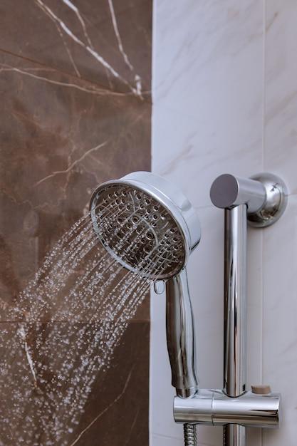 Frische dusche mit wassertropfenspritzen. wasser, das vom duschkopf und vom hahn im modernen badezimmer läuft. Premium Fotos