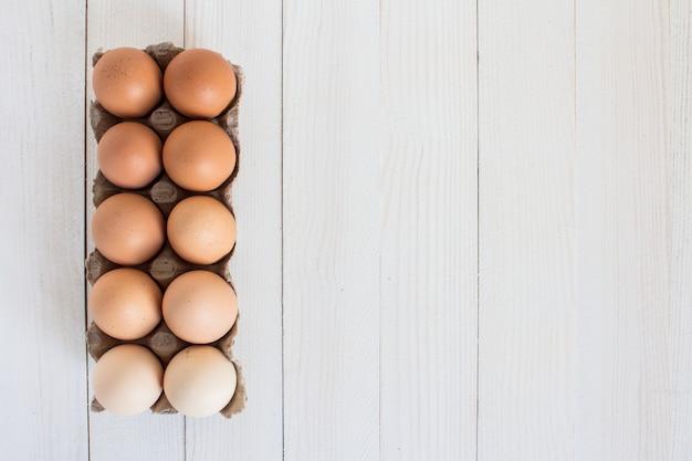 Frische eier im kartonpaket auf weißem holz Kostenlose Fotos