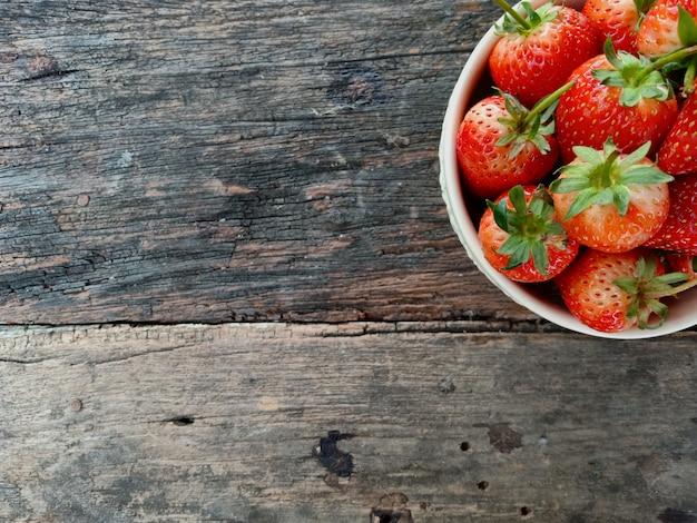 Frische erdbeeren in einer schüssel auf holztisch Premium Fotos