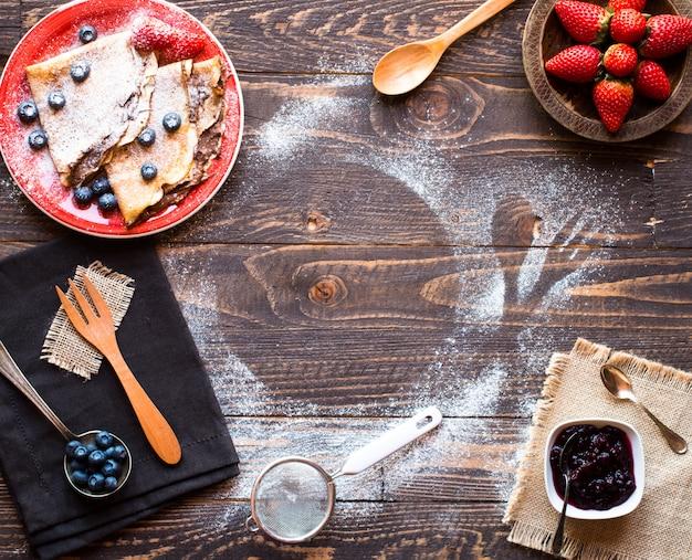 Frische erdbeerpfannkuchen oder -crepes mit beeren und schokolade Premium Fotos