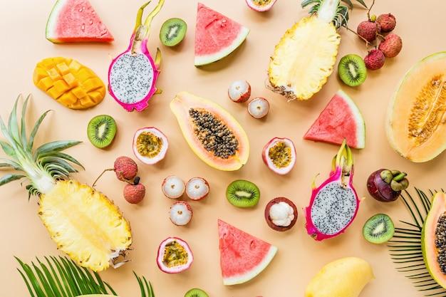 Frische exotische früchte und tropische palmblätter auf orange pastellhintergrund Premium Fotos