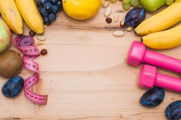 Frische früchte; trockenfrüchte; maßband und rosa hanteln auf holztisch Kostenlose Fotos