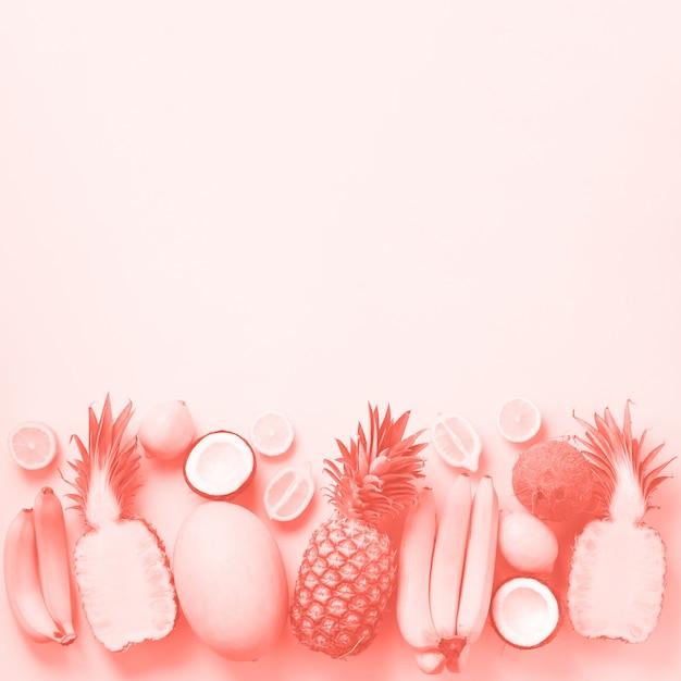 Frische früchte über sonnigem hintergrund. einfarbiges konzept mit banane, kokosnuss, ananas, zitrone, melone in der korallenroten farbe. ansicht von oben. kopieren sie platz. pop-art-design, kreatives sommerdesign. Premium Fotos