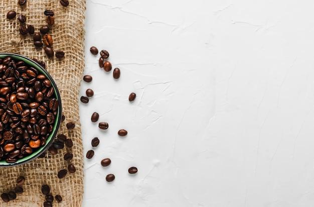 Frische, geröstete kaffeebohnen in einer tasse auf sackleinen Kostenlose Fotos