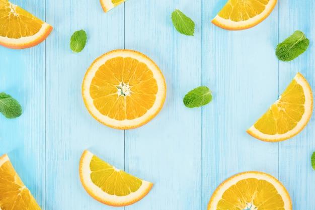 Frische geschnittene orangen mit pfeffer verlässt auf hellblauem hölzernem hintergrund Premium Fotos