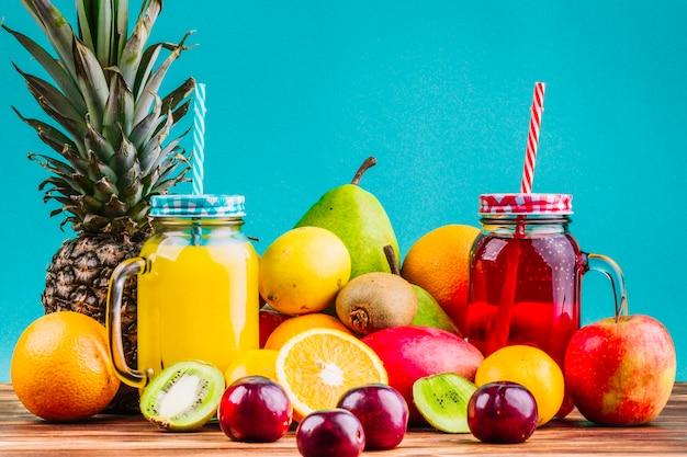 Frische gesunde früchte und saftmaurergläser auf tabelle gegen blauen hintergrund Kostenlose Fotos