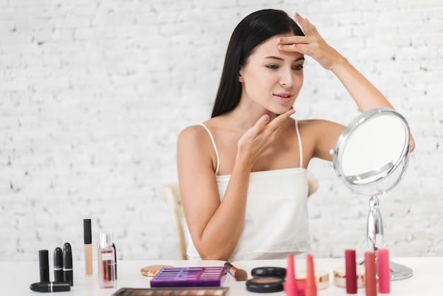 Frische gesunde haut der lächelnden jungen schönen frau, die auf spiegel mit make-up-kosmetik zu hause gesetzt schaut Premium Fotos