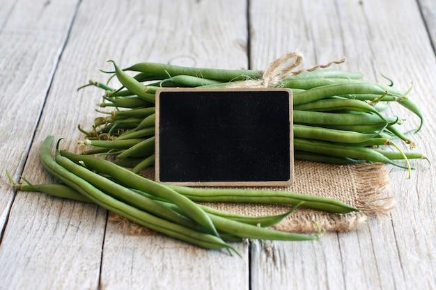 Frische grüne grüne bohnen mit einer kleinen tafel auf einem holztisch schließen oben Premium Fotos